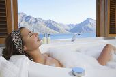 stock photo of bubble bath  - Side view of a young woman taking bubble bath with mountain lake outside window - JPG