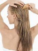 picture of hair comb  - Rear view of a young blond woman combing her wet hair against white background - JPG
