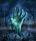 stock photo of zombie  - Zombie hand rising out of the ground in a spooky dark forest with creepy trees and fog as a symbol of Halloween imagination with a dangerous monster coming back from the dead - JPG