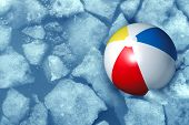 image of pool ball  - Cold summer weather concept with a plastic inflatabe beach ball stuck in frozen ice in a freezing pool as a symbol of leisure activity problems caused by colder temperatures during vacations and family holidays - JPG