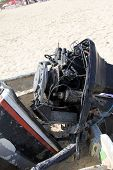 stock photo of outboard  - Old Disassembled Boat Outboard Motor on a sandy beach - JPG