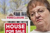 stock photo of eviction  - Depressed Senior Woman in Front of Foreclosure Real Estate Sign and House - JPG