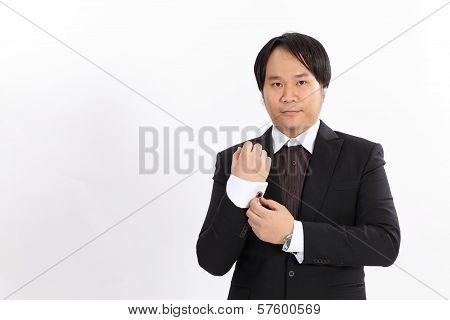 Isolated Of Business Man In Suit Correcting A Sleeve