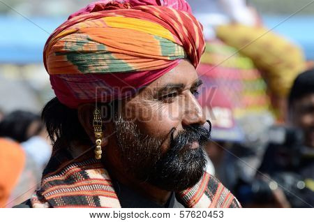 Rajput with bright turban and earring shows his moustache
