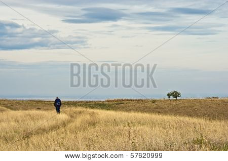 Lonely hiker is walking through flat prarie terrain