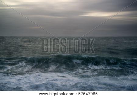 Moody Seascape Of Waves Breaking Under Stormy Winter Sky