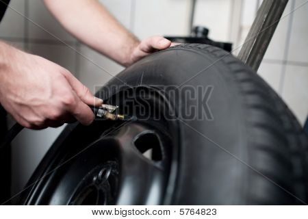 Mechanic Filling Air Into A Car Tyre.