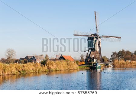 Old Dutch Windmill At The Edge Of A Small River