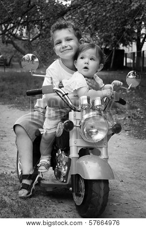 On The Street Hugging Brother Little Sister, They Ride On A Motorbike
