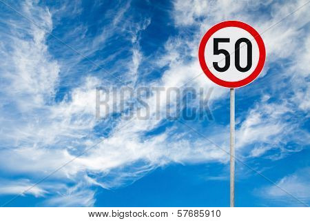 Round Speed Limit Road Sign Above Blue Cloudy Sky