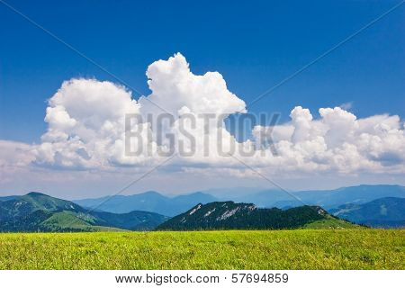 Beautiful white clouds in the blue sky over the mountains