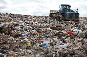 stock photo of landfills  - Garbage piles up in landfill site each day while truck covers it with sand for sanitary purpose