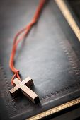 foto of holy-bible  - Closeup of simple wooden Christian cross necklace on holy Bible with copy space