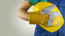 picture of labourer  - Workman wearing a protective glove holding a yellow hardhat or safety helmet conceptual of a builder construction worker tradesman or manual labourer - JPG