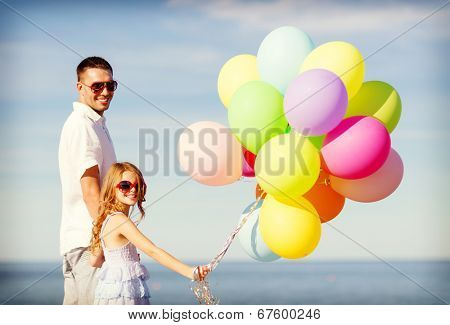 summer holidays, celebration, children and family concept - happy father and daughter with colorful balloons at seaside