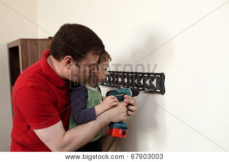 Father With Son Installing Mount Tv