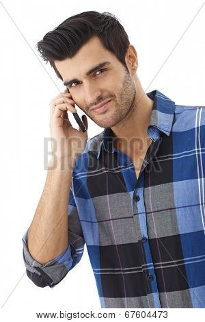 Happy young man talking on mobilephone, looking at camera.