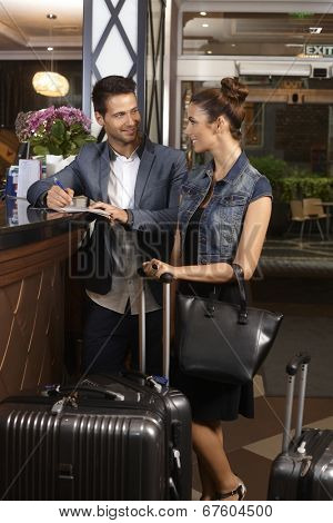 Young couple filling in check in form at hotel reception upon arrival, smiling happy.