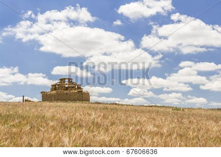 Ruined Adobe Pigeon House Between A Cereal Field And A Cloudy Blue Sky