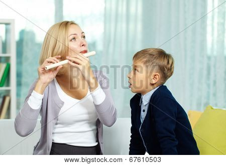 Portrait of female tutor playing the flute with her pupil near by