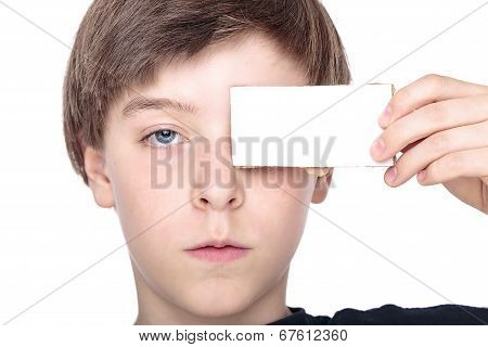 Portrait Of A Teenager Boy Holding A White Piece Of Cardboard In Front Of One Eye
