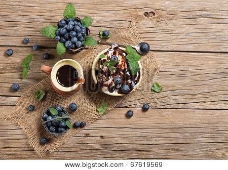 Ice Cream With Fresh Blueberries And Leaves From Top On Table