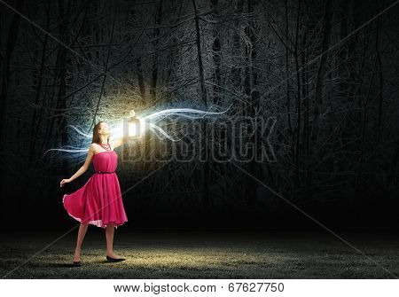 Young woman in red dress walking in night wood