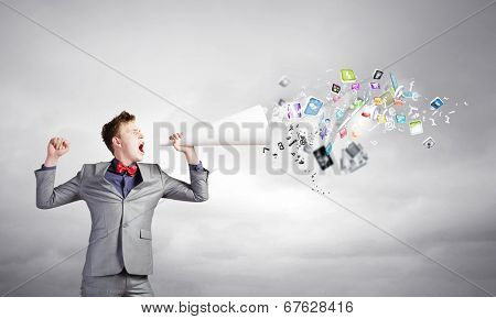 Young businessman speaking in trumpet and colorful icons flying out