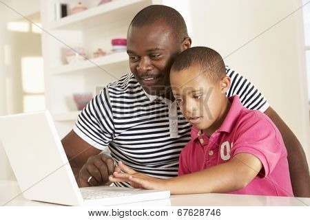 Father and Downs Syndrome son with laptop