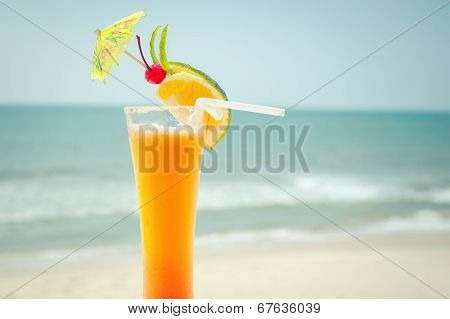 Tequila Sunrise Cocktail With Fruits And Umbrella Decoration At Tropical Ocean Beach
