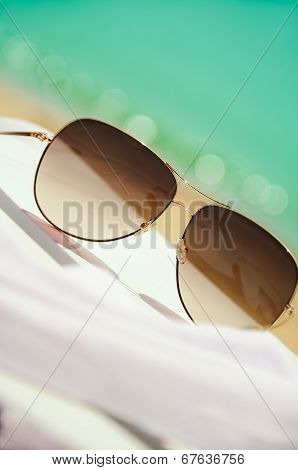 Sunglasses And White Chiffon Pareo On Background Of Sea And Sand Vertical