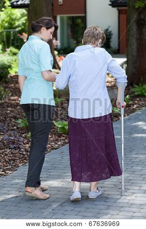 Woman On Crutches In A Garden