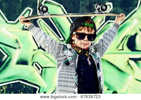Cool 7 year old boy with his skateboard on the street. Graffiti background. Childhood. Summertime.