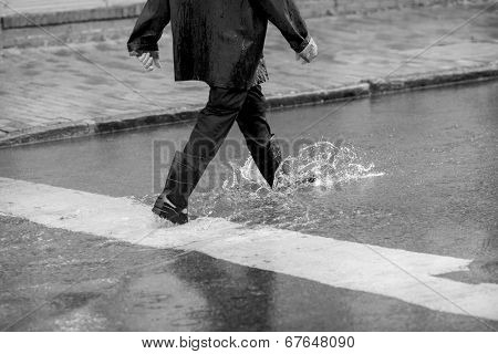 man walking in flooded street during downpour