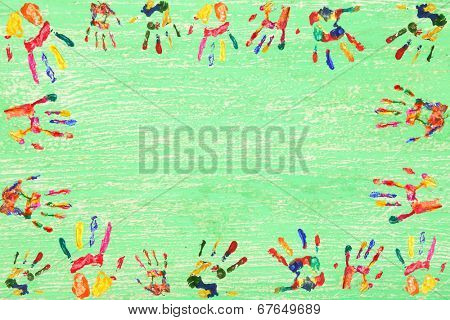 Frame of color hands print on wooden background