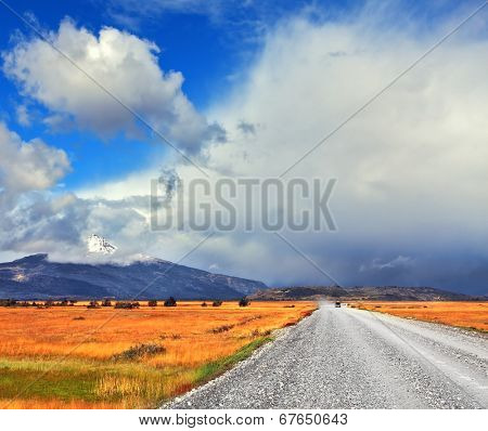 Strong wind drives the clouds. The dirt road in the endless pampas. On the horizon, the mountains visible in the haze