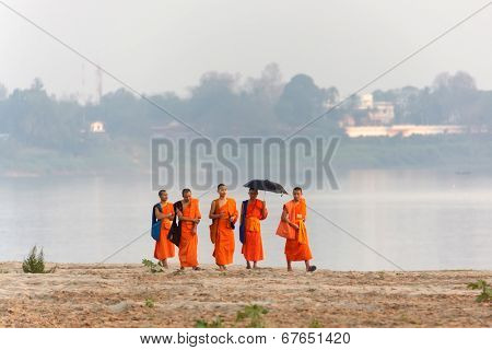 VIENTIANE,LAOS, February 14 : Unidentified Buddhist monks walking on the Mekong river's bank in Vientiane,Laos, on February 14, 2012