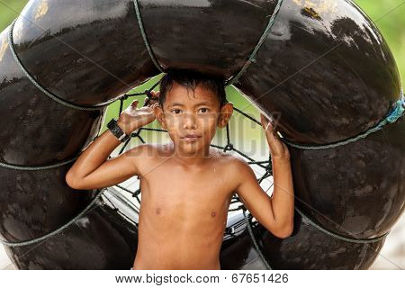 BUKIT LAWANG,INDONESIA, July 06 : Unidentified little boy holding a air tube for tubing in the river in the Bukit Lawang village, Sumatra, Indonesia, on July 06, 2010
