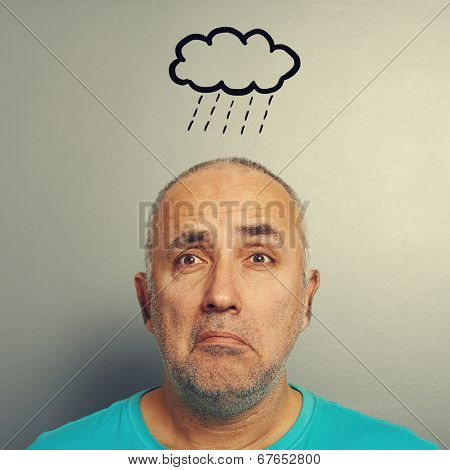 portrait of depressed senior man with drawing storm cloud over grey background