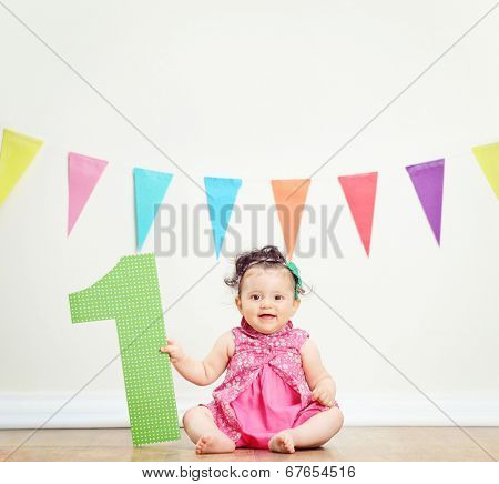 Cute baby girl celebrating her first birthday seated on the floor at home shot with tilt and shift lens