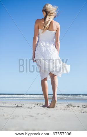 Blonde in white dress strolling on the beach on a bright day