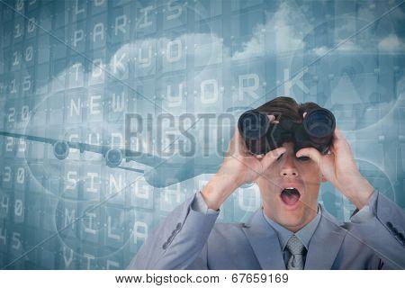 Suprised businessman looking through binoculars against departures board for major cities