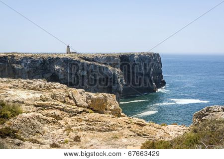 Rocky Coastline And Lighthouse In Sagres, Portugal