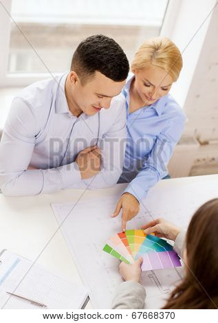 home, design and architecture concept - smiling couple looking at blueprint and color samples at office