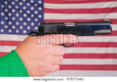 Close-up of a man's hand holding a cocked .45 ACP semi-automatic handgun infront of an American flag