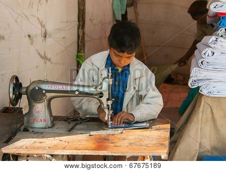 Child Labor, Boy Sewing In Booth On The Market.
