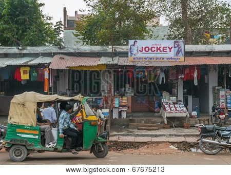 Street View With Small Shops And Motor Rickshaw.