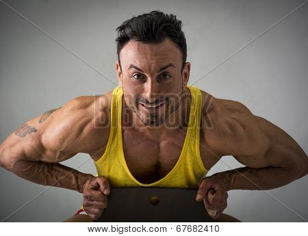 Muscular Man Sitting On Chair And Smiling