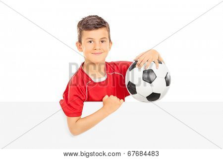Kid holding a football behind a blank panel isolated on white background