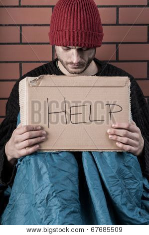 Man Begging On The Street With Help Sign